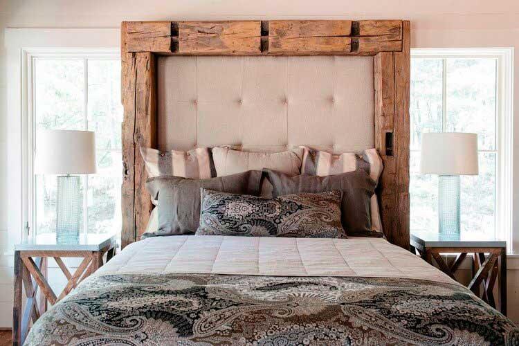 Изголовье кровати украшено грубым массивом дерева.