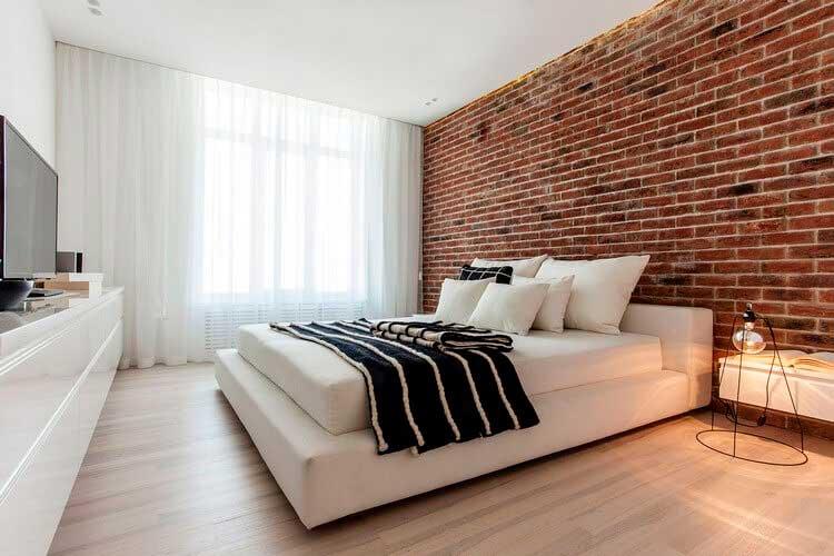 Терракотовая кирпичная стена создаёт стильный акцент в светлом оформлении спальни.